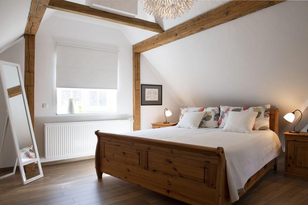 Großzügiges Bett unter originalen Dachbalken
